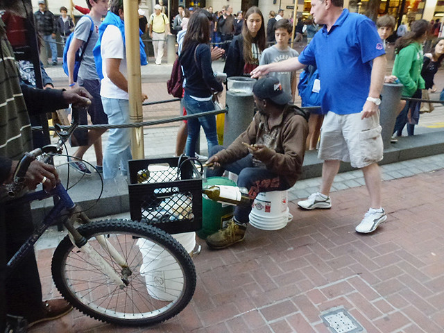 Passerby giving money to a semi-busker playing bottles on Market Street San Francisco
