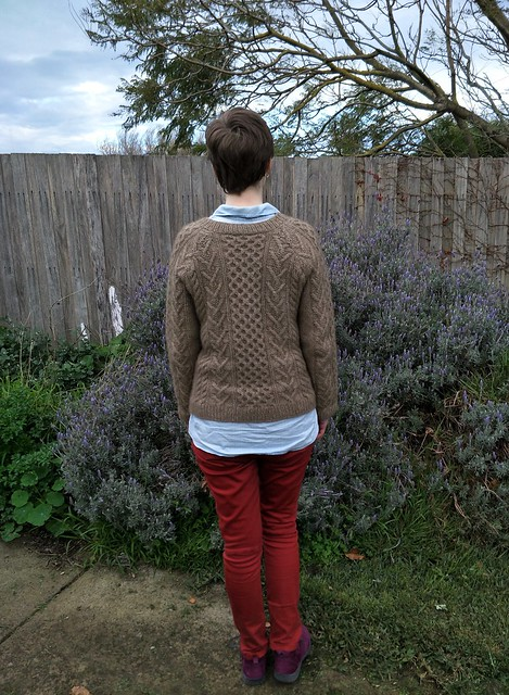 A woman stands in front of a garden fence. She wears a handknit cabled jumper, denim shirt, red jeans and purple suede boots.