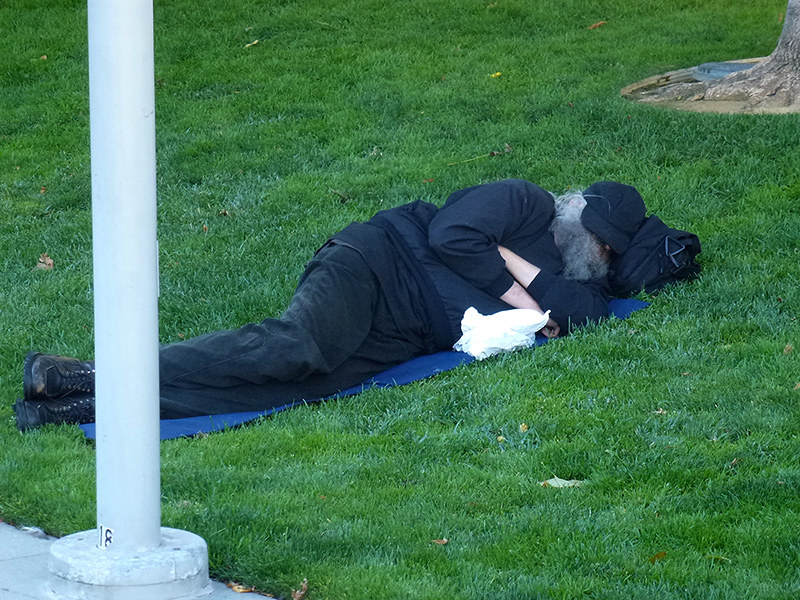 Homeless man sleeping in Jefferson Square Park in San Francisco