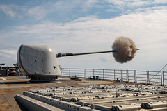USS Normandy fires its Mark 45 5-inch gun during a live-fire exercise.