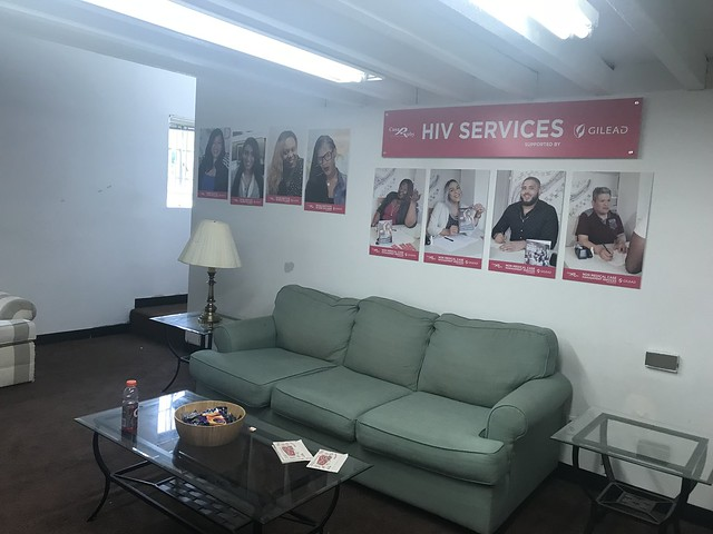 A photo of a drop-in center with a table and a couch. The information of case managers are on the wall
