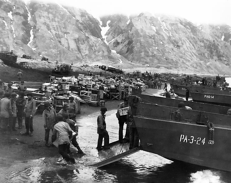 Soldiers unload landing craft on the beach at Massacre Bay, Attu, Alaska, on May 13, 1943. LCVPs in the foreground are from USS Zeilin (APA-3) and USS Heywood (APA-6).. U.S. Naval Historical Center Photo #: 80-G-50921