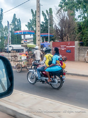 A motorcycle taxi with a woman and her child as passenger, Abomey Calavi, Benin