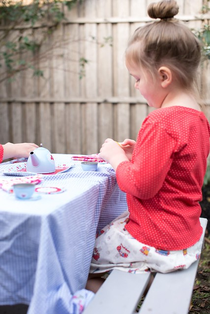 A girl sits at a picnic table outside.