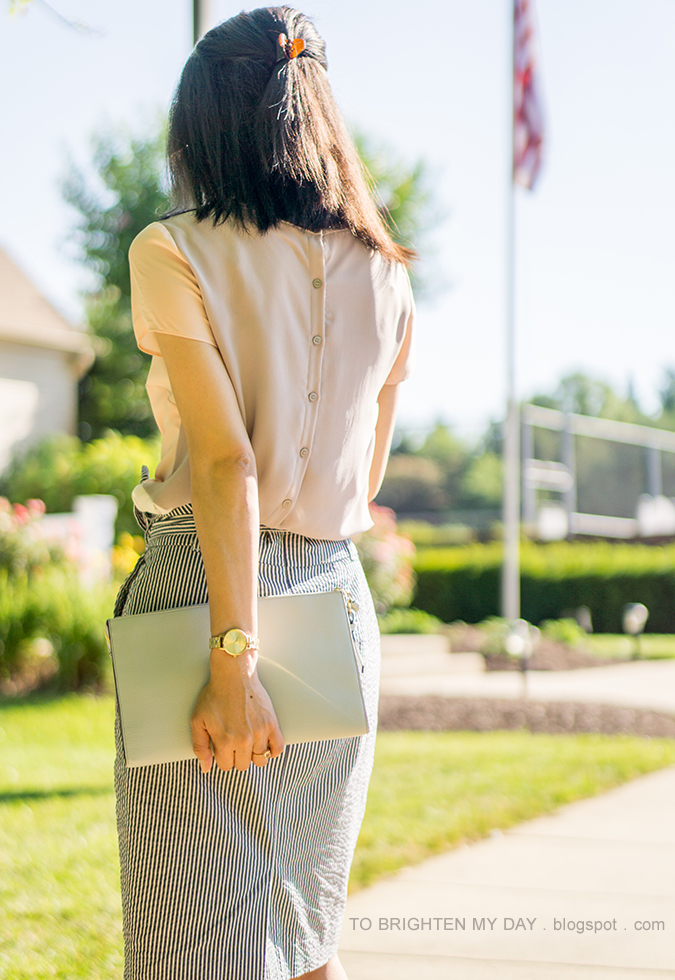 color blocked top with button back, blue striped pencil skirt with waist tie, grey blue clutch, gold watch