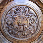 Wooden carving of a shield on a door of the Salt Lake Temple with the acronym HTTL, meaning 'Holiness To The Lord'.