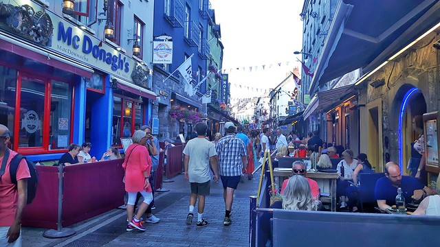 lots of people wandering along Quay Street, Galway