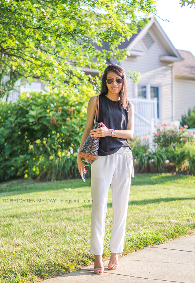 black silk sleeveless top, two tone watch, silver cuff, patterned tote, white cropped pants with waist tie, nude sandals