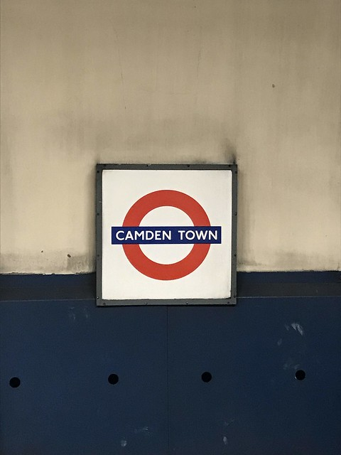 """A white sign with a red circle on blue wall that reads """"Camden Town."""""""