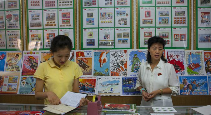 North Korean sellers in a stamps shop in North Hwanghae Province, Kaesong, North Korea. A wide variety of anti-U.S. propaganda stamps are on display. Photo by Eric Lafforgue on September 8, 2012-09-08 - from NKNews dot org