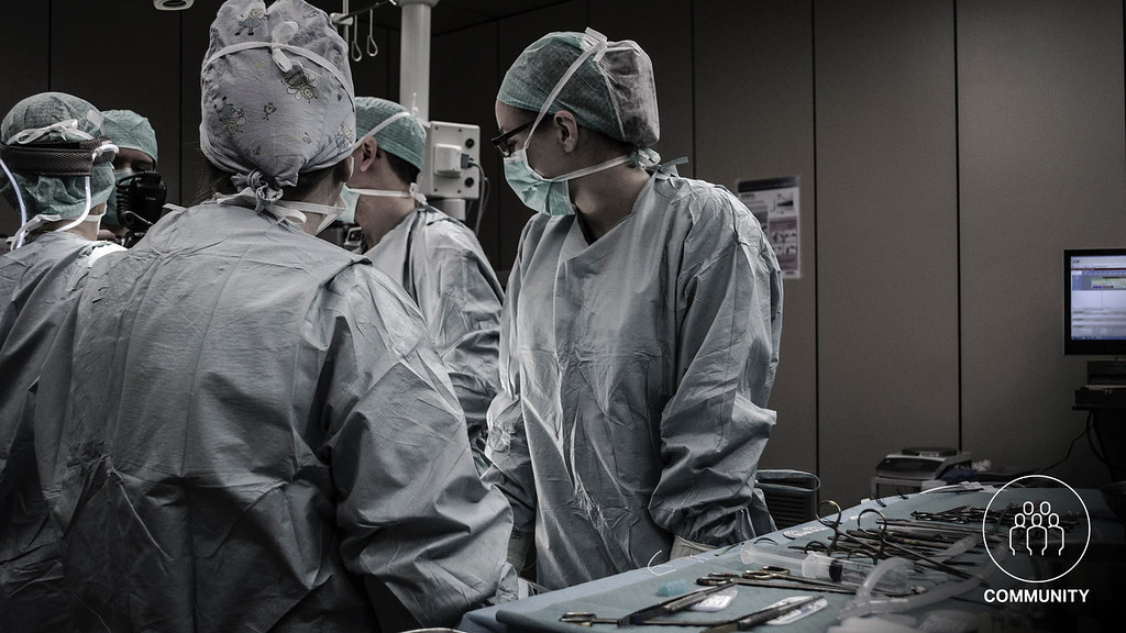 Five surgeons standing around an operating table