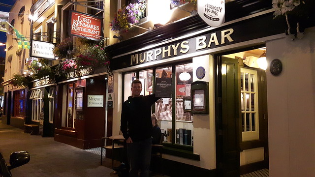 A man standing outside of an Irish Pub called Murphy's Bar at night.