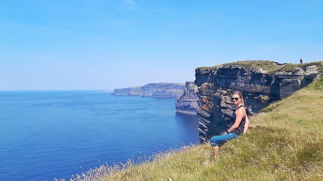 Claire sitting at the top of high Cliffs of Moher, Ireland.
