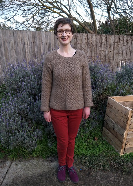 A woman stands in front of a garden fence. She wears a handknit cabled jumper, red jeans and purple boots. She is smiling.