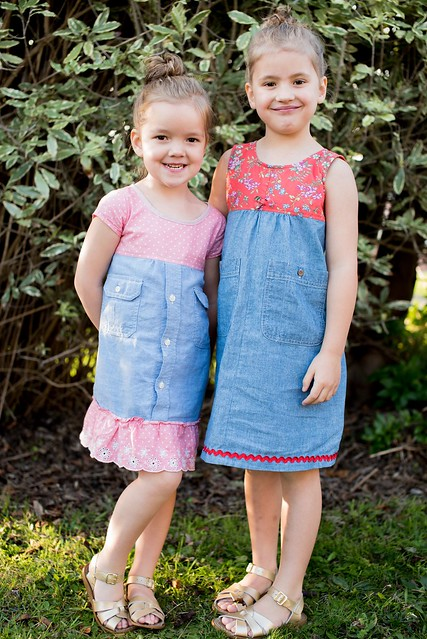Two girls stand in a garden, wearing handmade dresses.