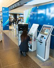 Alaska Airlines Staffer Fixing Boarding Pass Machine