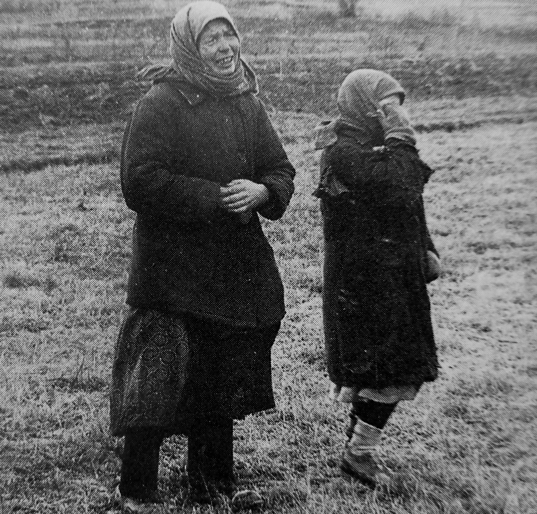 1942. Женщина и девочка плачут, глядя на тело повешенного мужчины