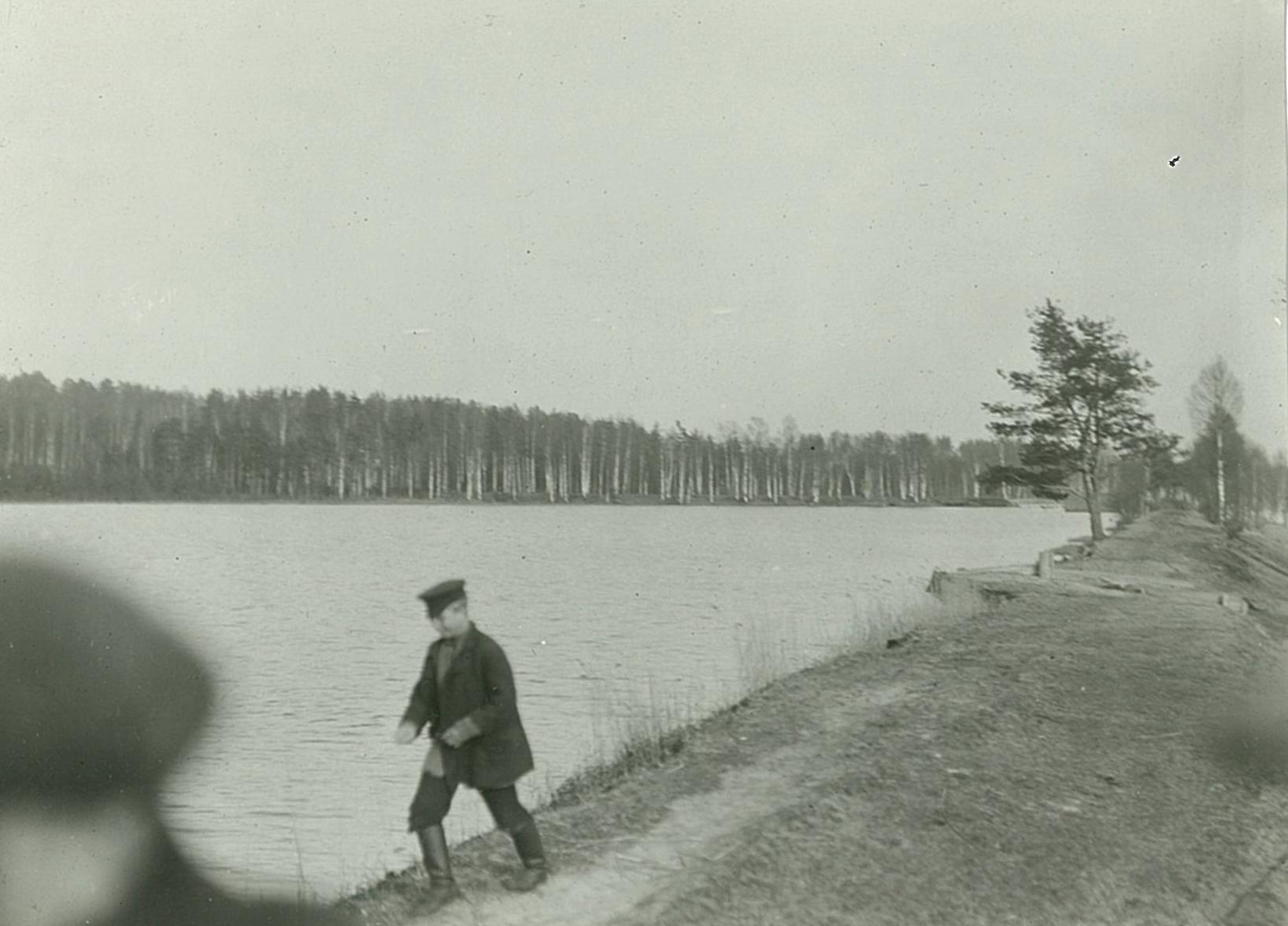 Подросток, идущий вдоль берега озера