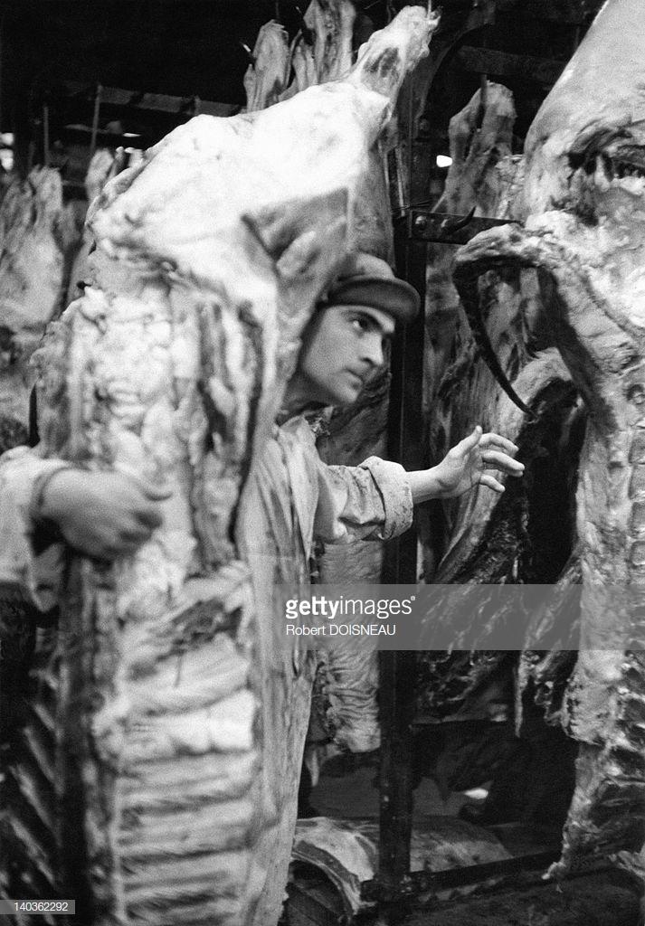 1955. Рыночный носильщик в мясном зале рано утром в Ле-Аль