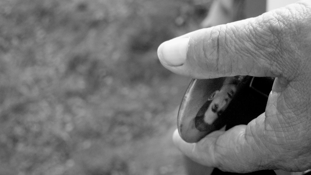 Hand holding old photo of a soldier