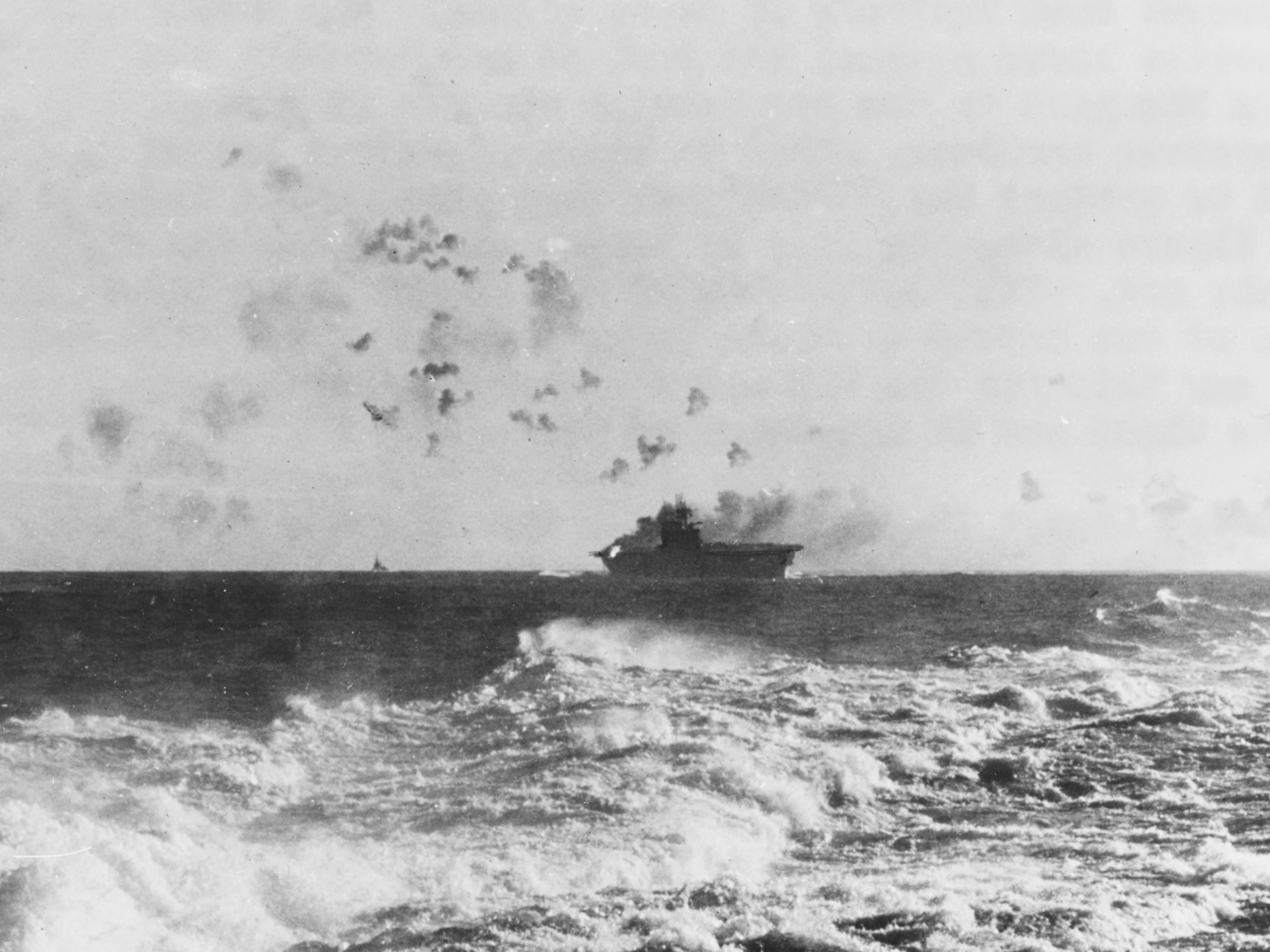 The U.S. Navy aircraft carrier USS Enterprise (CV-6) seen from another U.S. ship while under attack by Japanese dive bombers during the Battle of the Eastern Solomons on August 24, 1942. An intense fire is burning in her starboard after five-inch gun gallery, the result of a bomb hit that ignited ready-service ammunition. Note the anti-aircraft shell bursts over the carrier.