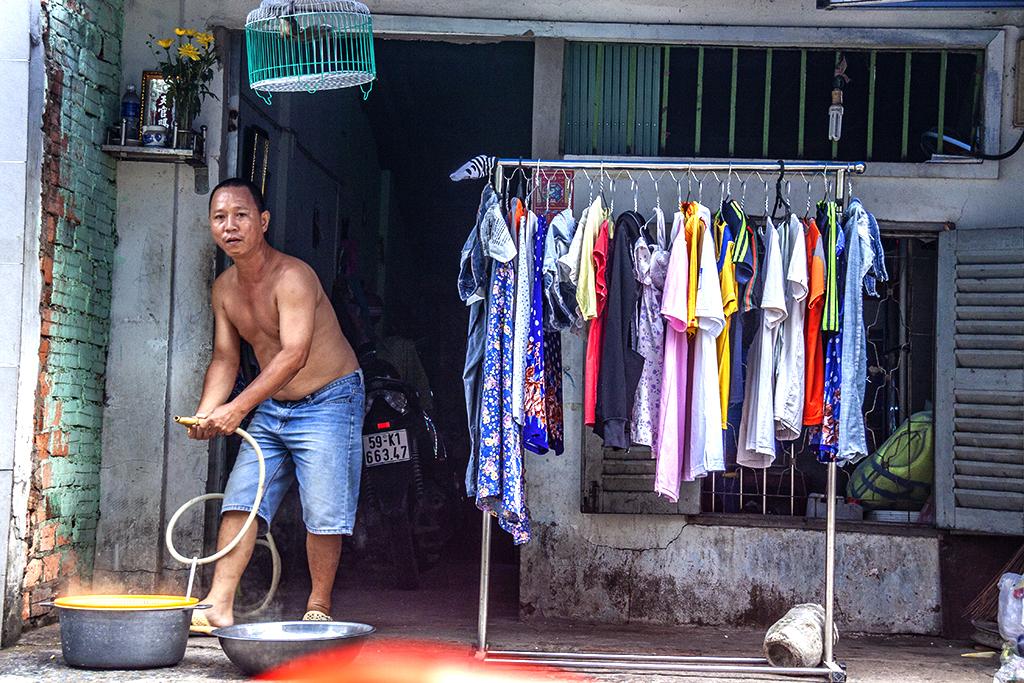 Shirtless man, bird cage and drying laundry--Saigon