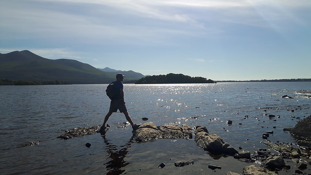 Man standing on rocks in the lake in Killarney National Park, Ireland.