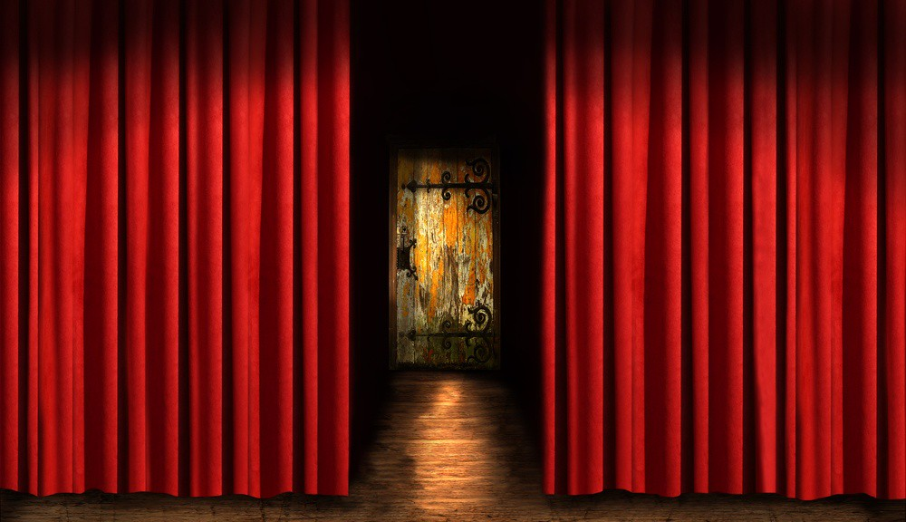 wooden stage, red curtain, and ominous door