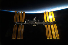 The International Space Station backdropped by Earth's horizon and the blackness of space. Original from NASA . Digitally enhanced by rawpixel.