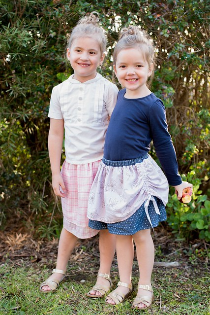 Two girls stand in a garden, wearing homemade skirts and tops.