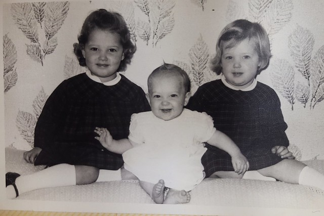3 little girls sitting on a cushion against a wall. Two older ones on either side of a baby. The one on the left has dark, curly hair and brown eyes, the giirl on the right has straight, blond hair and blue eyes. Dressed in their best clothes, they are all smiling