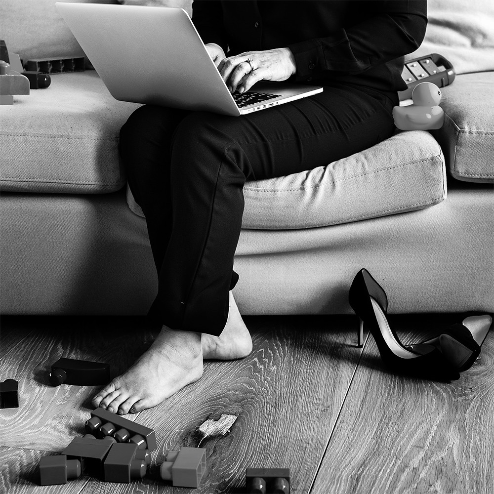 A woman on a sofa using a laptop. There are lego and shoes on the floor.