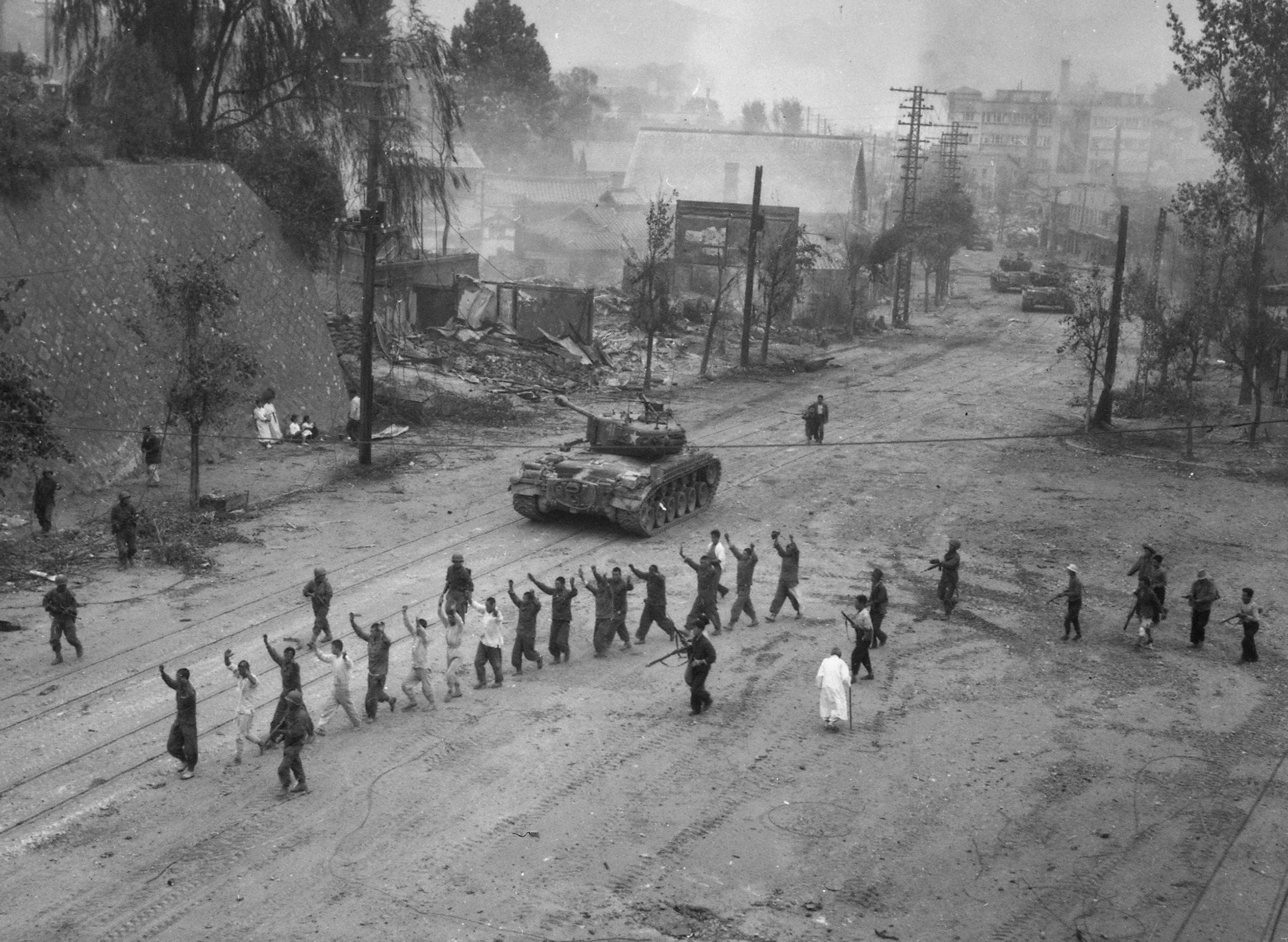 American M26 Pershing tanks in downtown Seoul, South Korea, in the Second Battle of Seoul during the Korean War in September 1950. In the foreground, United Nations troops round up North Korean prisoners-of-war.