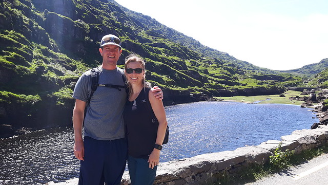 A couple standing in front of a lake surrounded by green hills in Ireland. Gap of Dunloe, Killarney