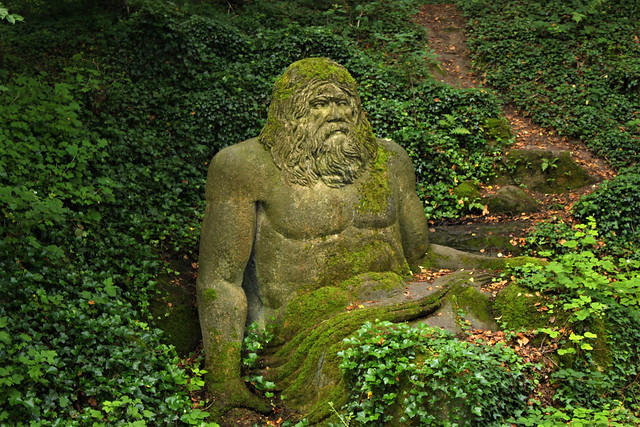 statue of poseiden in forest