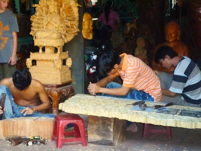 Carvers working on a traditional Buddhist Wooden Panel depicting Hindu scenes in Hoi An in Vietnam
