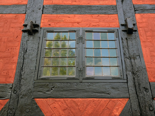 Leaded window in an old half-timbered building painted in red ochre in Den Gamle By, recreated villages set in different times, in Aarhus, Denmark