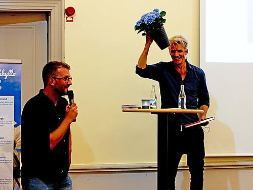 Blomkrukan som Pelle Sandstrak skämtade med under sin föreläsning överlämnades till honom av kultursekreterare David Strenge Wingren. - Tack, en blå blomma, blått är livet, sa Pelle.