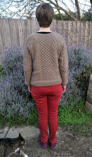 A woman stands in front of a garden fence. She wears a handknit cabled jumper, red jeans and purple boots. A cat creeps into frame.