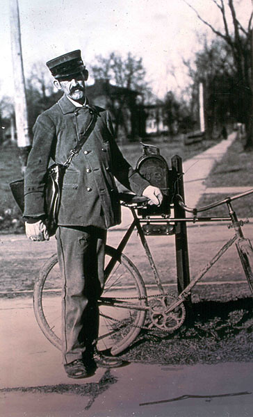 City letter carrier, circa 1890, with the bicycle he used on his rounds.