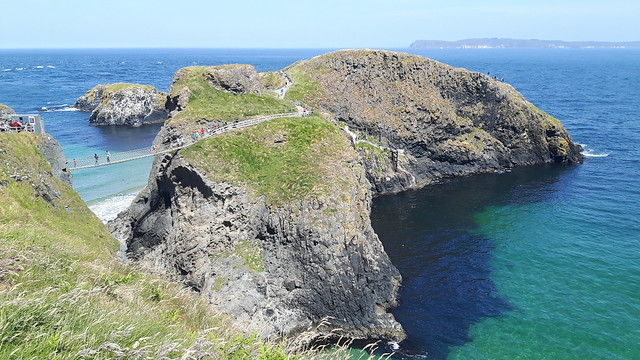 A rope bridge high above the turquoise water in Ireland to a small island.