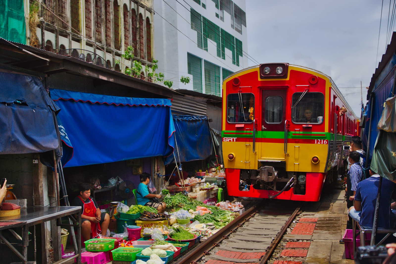Mae Klong railway market with passing train in Samut Songkhram province in Thailand