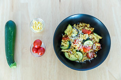 Top view of golden brown roasted spaetzle with dried tomatoes and zucchini including ingredients