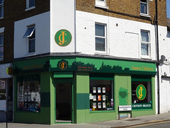 "The previous shopfront, repainted in several shades of green with a stylised city skyline above the windows.  A new logo consisting of an intertwined ""J"" and ""C"" has been added above the door, on the corner of the first floor of the building, and on one of the windows."