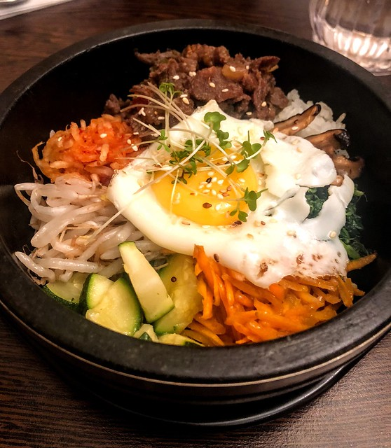 A bowl of Jihwaja. Bean sprouts, cucumber, shredded carrots and beef are topped with a fried egg.