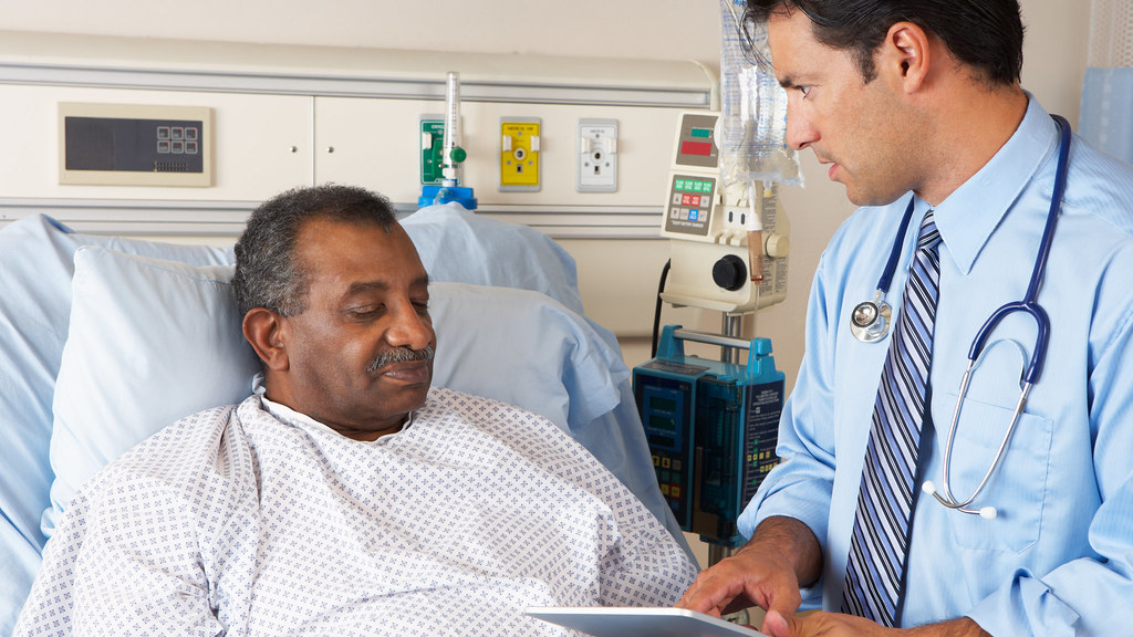 A patient in a hospital bed speaking to a doctor