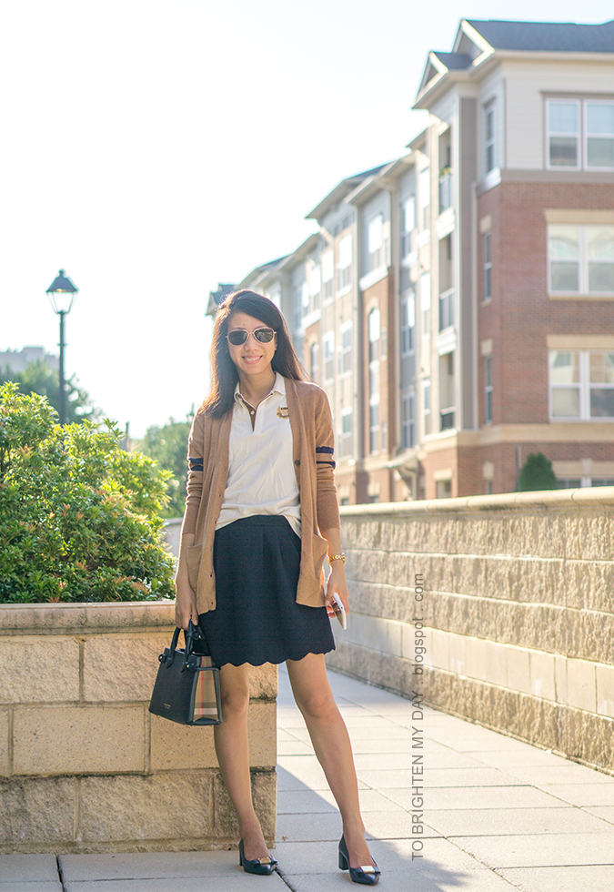 camel long varsity cardigan, polo with crest emblem, navy scallop skirt, gold watch, navy tote, navy bow pumps with block heel
