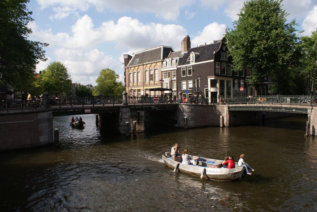 Vue sur un canal d'Amsterdam parcouru par des bateaux en toute décontraction.