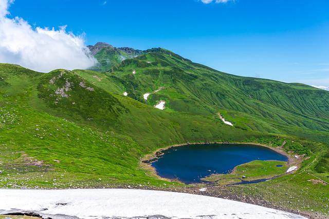 雪渓越しに鳥海湖と新山