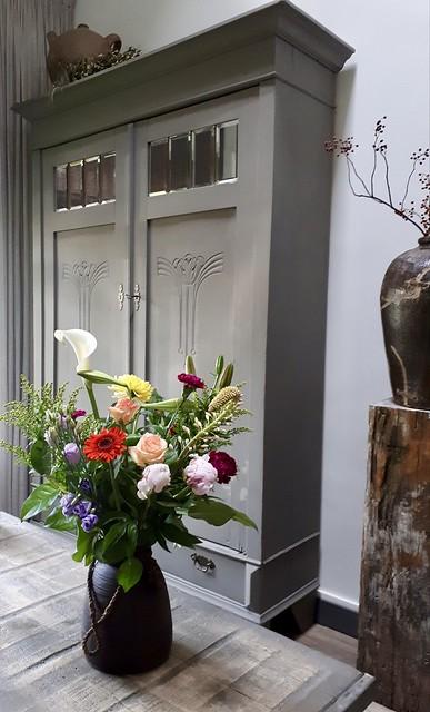 Bloemen in kruik kast landelijke stijl